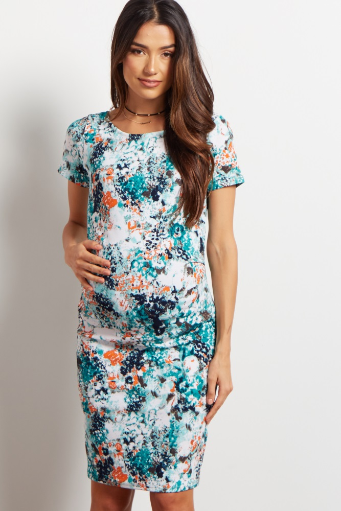 A floral printed fitted short sleeve maternity dress. Rounded neckline. Ruched at sides.