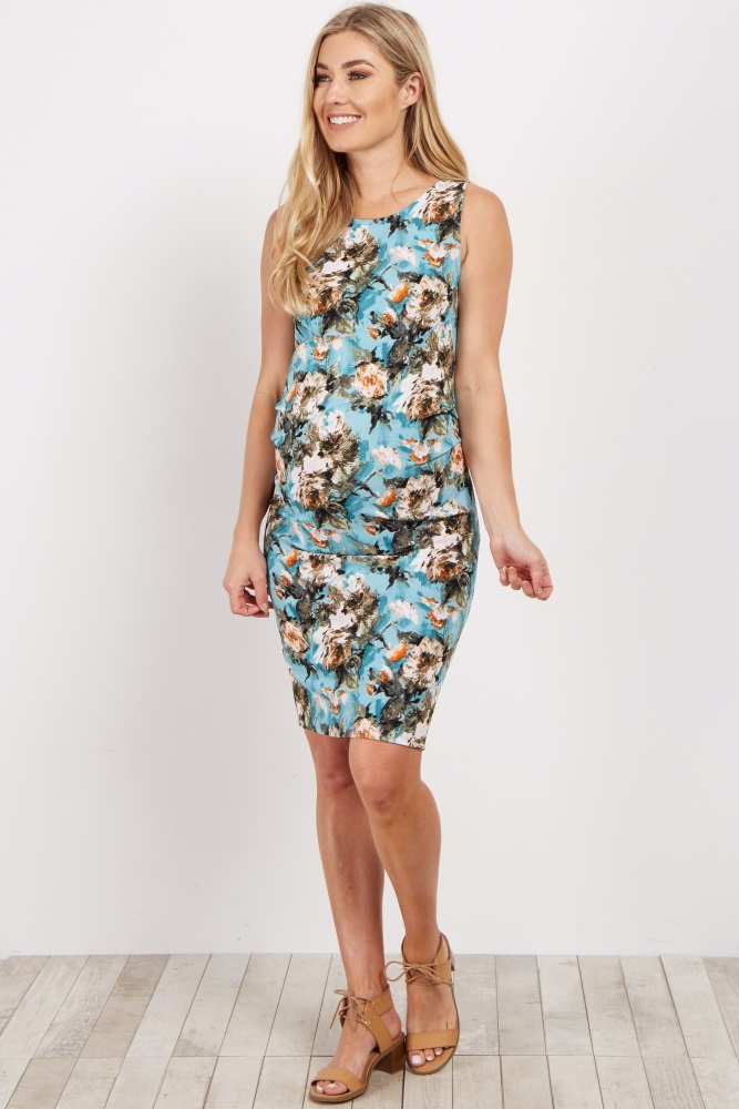 An abstract floral printed fitted sleeveless maternity dress. Rounded neckline. Ruched at sides.
