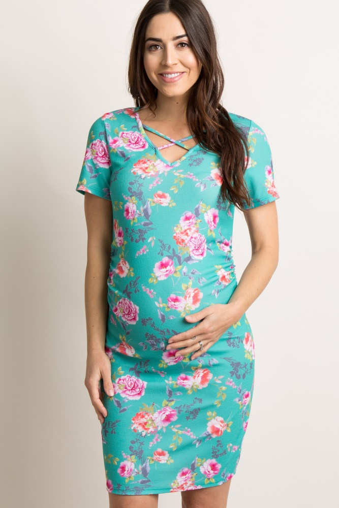 A floral short sleeve fitted maternity dress. V-neckline with crisscross accent. Ruched sides.